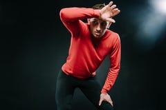 放松在坚硬锻炼以后的英俊的严肃的人运动员画象在健身房,在头上把他的手放 运动的人佩带的红色 免版税图库摄影