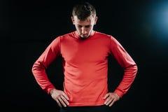 放松在坚硬锻炼以后的年轻运动员的画象身体在他的腰部生活方式的黑暗的背景、身分和藏品手, 库存照片