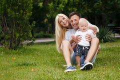 放松在夏天公园的愉快的家庭 免版税图库摄影