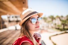 放松在夏天在帽子和太阳镜的太阳wearind的晴朗的女孩画象 夏天职业 免版税库存照片