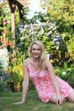 放松在夏天庭院里的可爱的少妇 免版税图库摄影