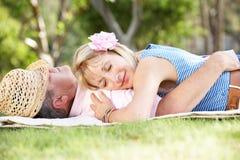放松在夏天庭院里的高级夫妇 库存图片