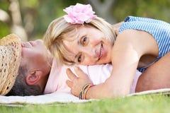 放松在夏天庭院里的高级夫妇 免版税库存照片