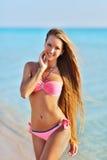 放松在夏天海滩的性感的比基尼泳装的美丽的妇女 免版税图库摄影