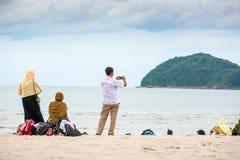 放松在夏天黄昏的沙滩的穆斯林家庭的背面图 库存图片