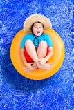 放松在夏天水池的愉快的年轻男孩 免版税图库摄影