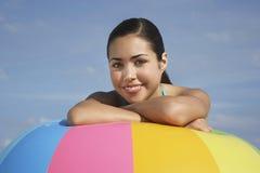 放松在大五颜六色的海滩球的十几岁的女孩 免版税图库摄影