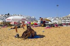 放松在太阳伞的树荫下的一对年长夫妇在沙滩的在Albuferia在葡萄牙 免版税图库摄影