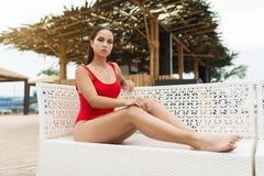 放松在太阳懒人的泳装的少妇在水池附近 库存图片