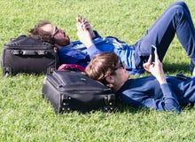 放松在奇迹广场草的两个游人有h的 免版税库存照片