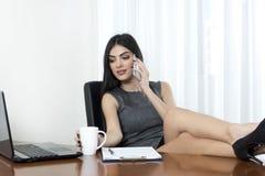 放松在她的办公室的女商人 免版税库存照片