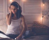 放松在她的床上的少妇,她听到音乐 免版税库存照片