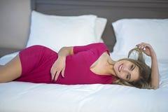 放松在她的床上的逗人喜爱的妇女 免版税库存照片