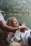 放松在她的男朋友膝部的妇女 免版税库存照片