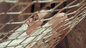 戴放松在她的顶楼公寓的吊床的短发佩带的眼镜的妇女 影视素材