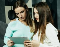 放松在客厅的两个美丽的少妇难倒看便携式计算机 库存照片