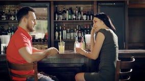 放松在客栈的年轻夫妇坐在酒吧柜台和喝beverageMen,并且在便衣打扮的妇女是 股票录像