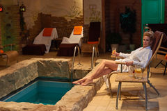 放松在室内游泳池的白肤金发的妇女 免版税图库摄影