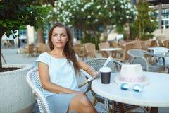 放松在室外咖啡馆的妇女-饮用的咖啡和读 图库摄影