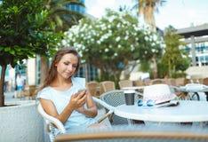 放松在室外咖啡馆-饮用的咖啡和使用a的妇女 免版税库存照片