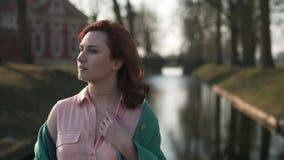 放松在宫殿零件运河附近的年轻女人在穿绿色时尚夹克-红头发人的温暖的春天天气期间 股票视频