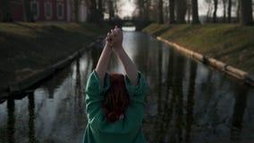 放松在宫殿零件运河附近的年轻女人在穿绿色时尚夹克-红头发人的温暖的春天天气期间 影视素材