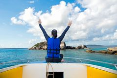 放松在小船和看Similan安达曼群岛,泰国的后面观点的旅客妇女 背景蓝天 免版税库存照片