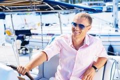 放松在小船的一个愉快的白肤金发的人的画象 免版税库存图片