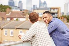 放松在屋顶庭院饮用的咖啡的两个男性朋友 免版税库存图片