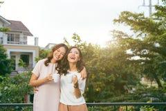 放松在屋顶庭院饮用的咖啡的两名妇女 免版税库存图片