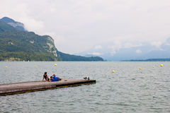 放松在山湖的一个码头的一对年轻夫妇 免版税库存图片