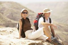 放松在山顶部的远足者 免版税库存图片