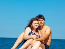 放松在岩石的恋人或家庭夫妇  免版税库存图片