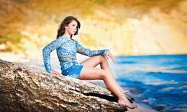 放松在岩石的美丽的女孩在海运附近 免版税库存图片