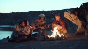 放松在岸的篝火的旅客 免版税库存照片