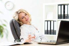 放松在工作的资深女商人在办公室 免版税库存照片