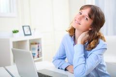 放松在工作的年轻微笑的女商人 免版税图库摄影
