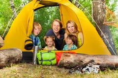 放松在帐篷里面的愉快的年轻家庭在森林 库存照片