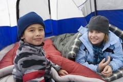 放松在帐篷里面的男孩和姐妹 库存图片