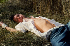 放松在干草的牛仔裤的年轻人 免版税图库摄影