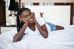 放松在床上的一名微笑的俏丽的年轻非洲妇女的画象 库存照片