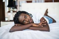 放松在床上的一名微笑的俏丽的年轻非洲妇女的画象 图库摄影