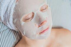 放松在床上的年轻红发妇女 在她的面孔的板料面具 免版税库存图片