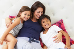 放松在床佩带的睡衣的母亲和孩子 免版税库存照片