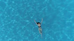 放松在度假,飞行在年轻性感的女孩的寄生虫说谎在透明的水池的水面的比基尼泳装的 股票视频