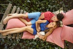 放松在庭院吊床的年轻夫妇 库存图片