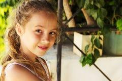 放松在庭院的逗人喜爱的青少年的女孩画象  免版税库存照片