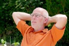 放松在庭院里的一个成熟人的画象 免版税库存图片