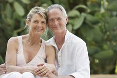 放松在庭院里的愉快的夫妇 图库摄影