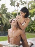 放松在庭院里的愉快的年轻夫妇 免版税库存图片